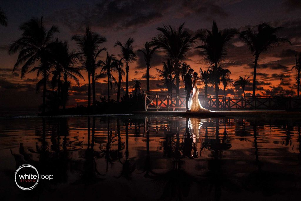 The groom and the bride in formal dress are posing for a sunset shot on the border of a pool where are reflected the palms.