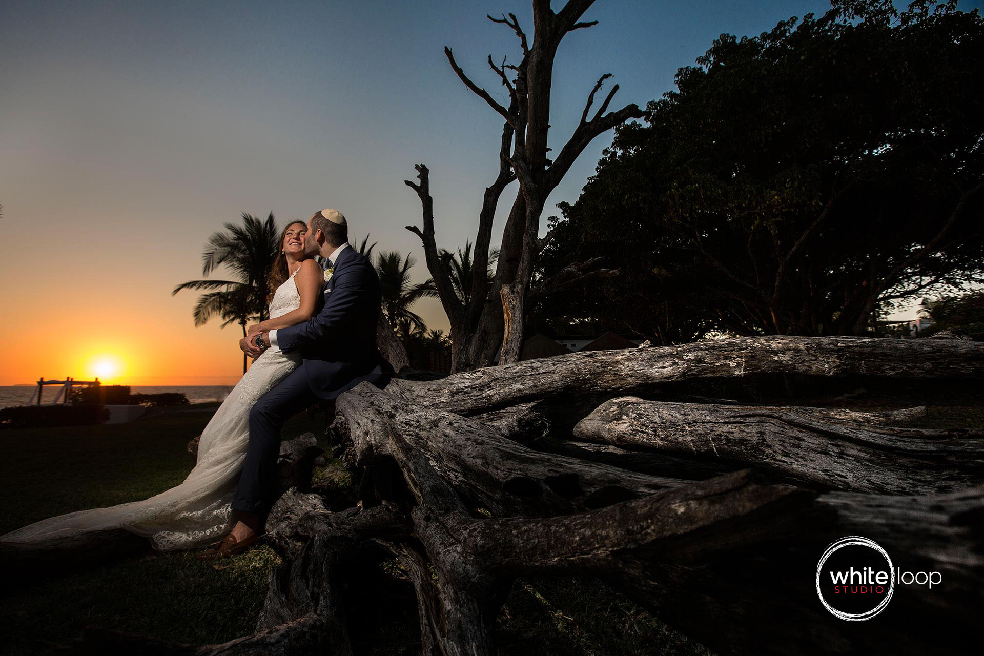 Bride and groom sitting on a big old trunk left on the beach, sunset behind