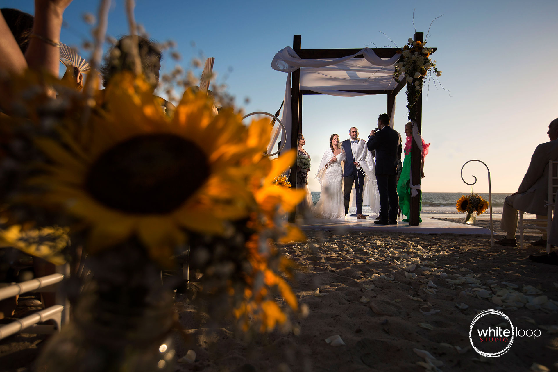 Bride and groom captured during an important moment of the Jewish Ceremony taking place on the beach during the sunset