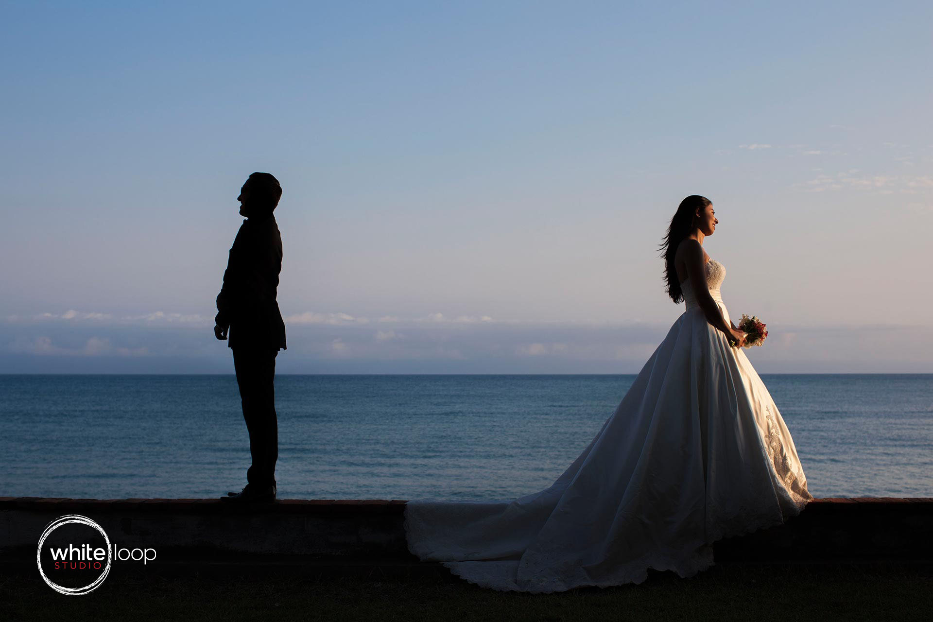 bride and groom are standing, bride facing the sunset and groom on the shadow, representing the opposites.