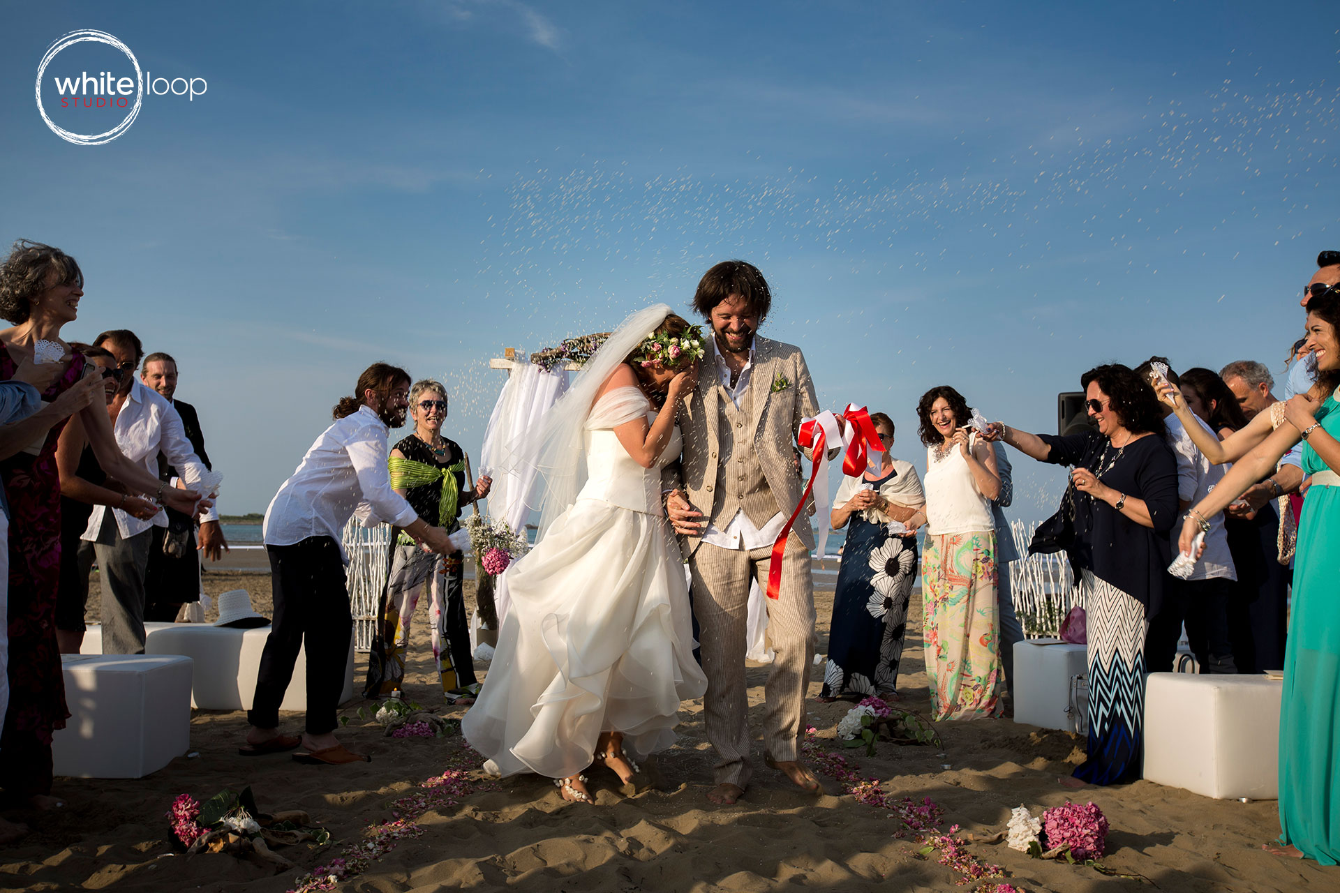 bride and groom standing on a wooden bridge suspended on the see on Lignano Sabbiadoro and facing the sunset