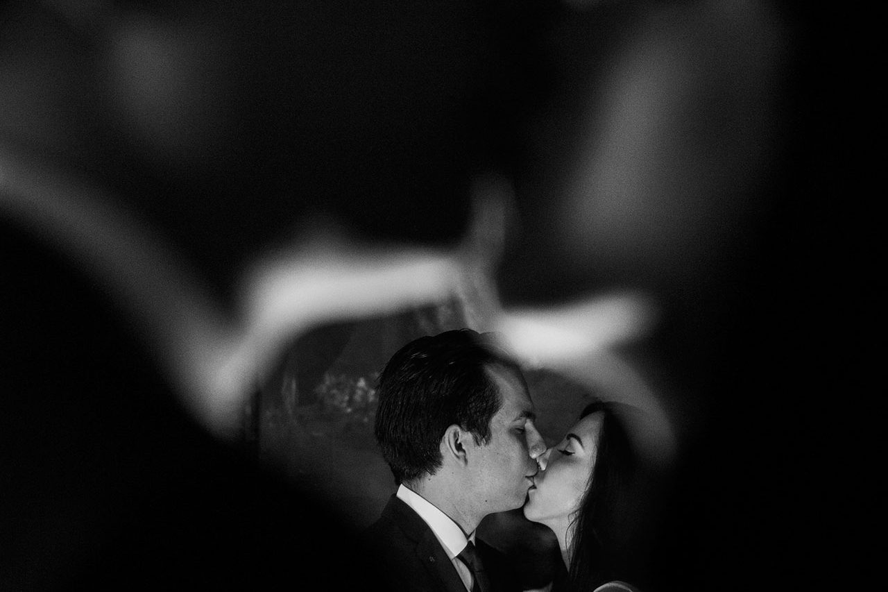 The bride and groom captured in the instant of a romantic kiss in black and white, describing the beautiful elegance and simplicity of love.
