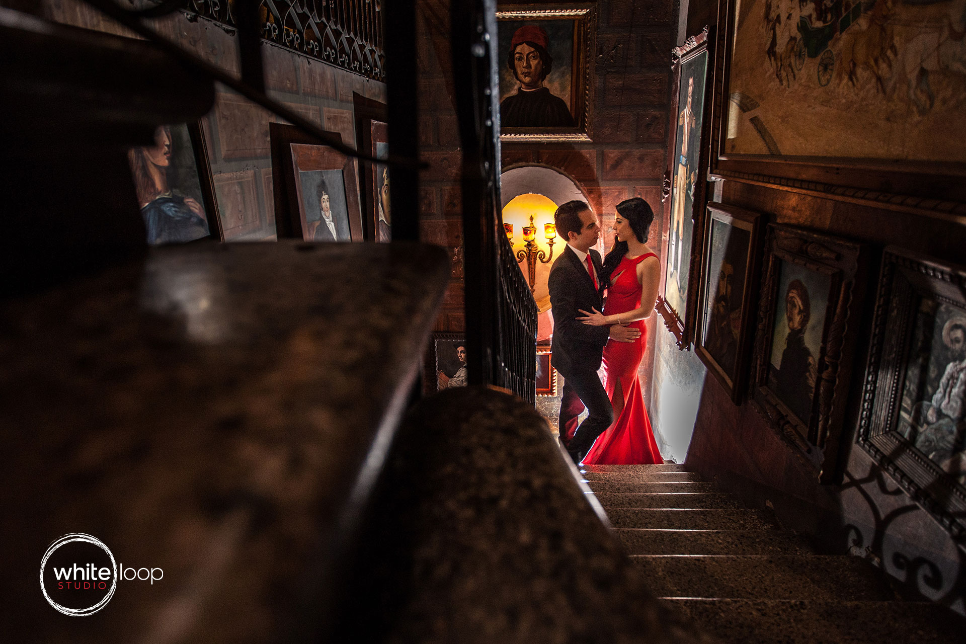 The bride and groom holding each other in the hallway surrounded by artistic paintings.
