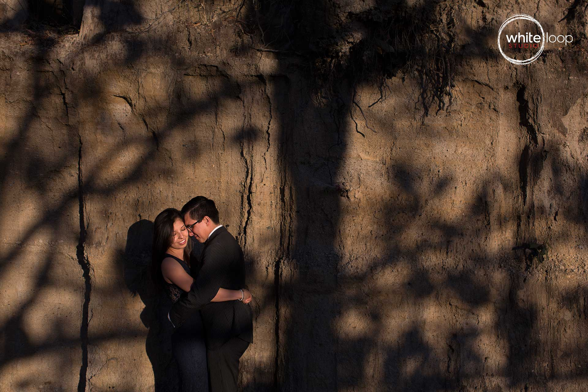 The bride and groom embraced with illuminations of the sunlight through the woods.