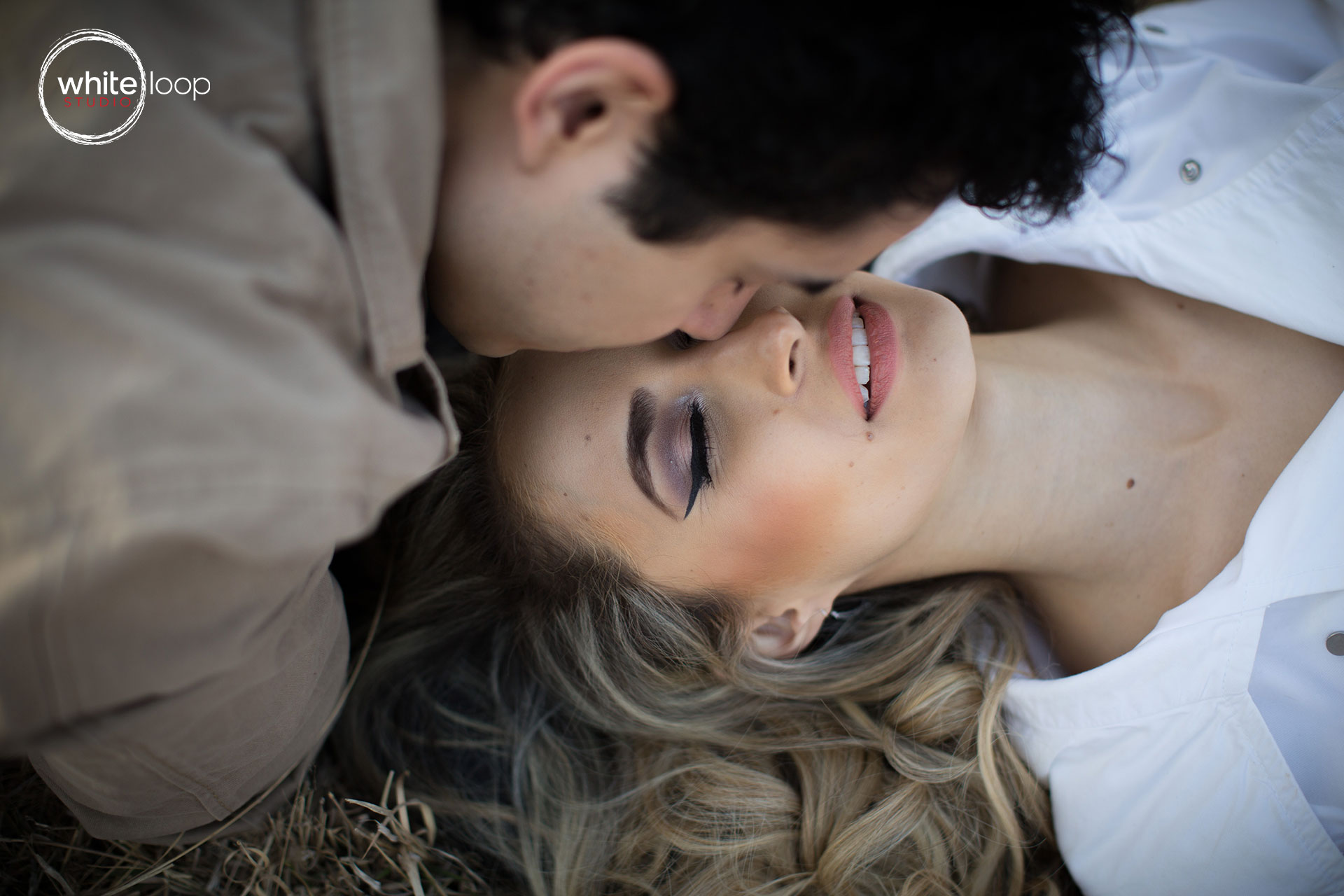 The groom kissing the bride on the forehead lying on grass, enjoying the moment with eyes closed