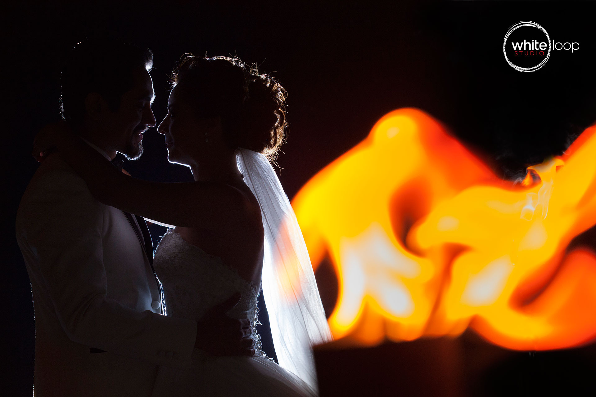 Groom and bride embracing eye to eye in a dark room with a lamp, keeping the couple against the light, exposing their silhouettes.