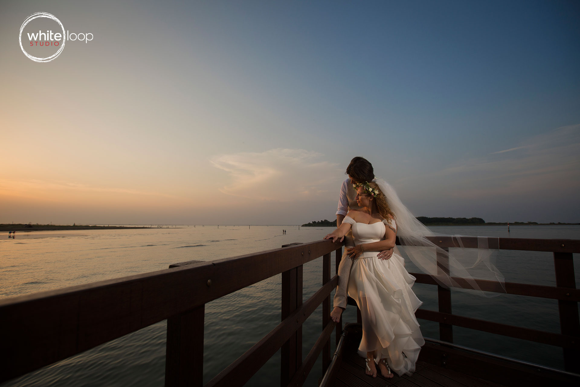 The bride and groom holding each other on a dock watching the sunset on the horizon of the sea.