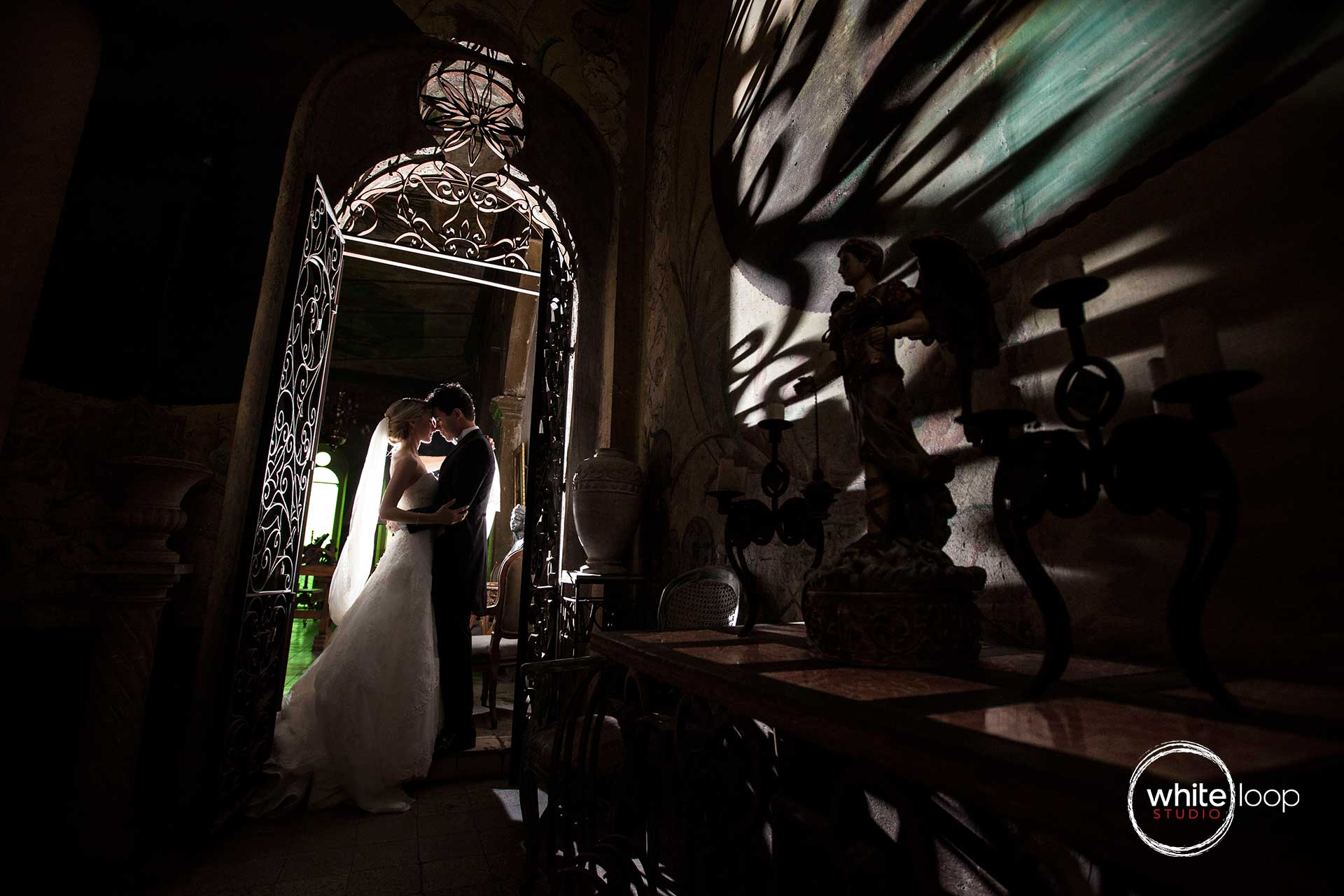 The bride and groom backlit embraced in one of the main doors of this house.