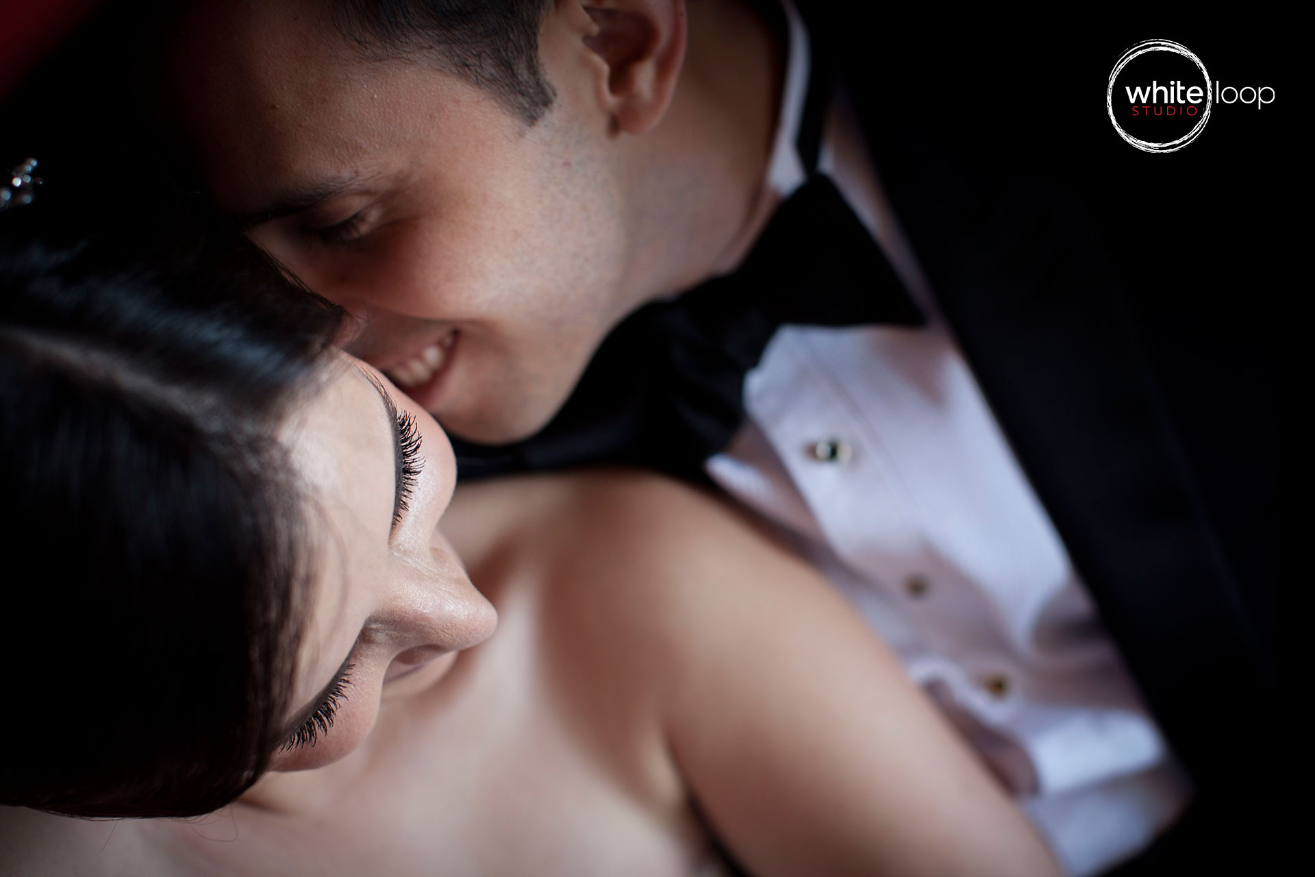 Photography of bride and groom taken from above, capturing the moment before an affectionate kiss.