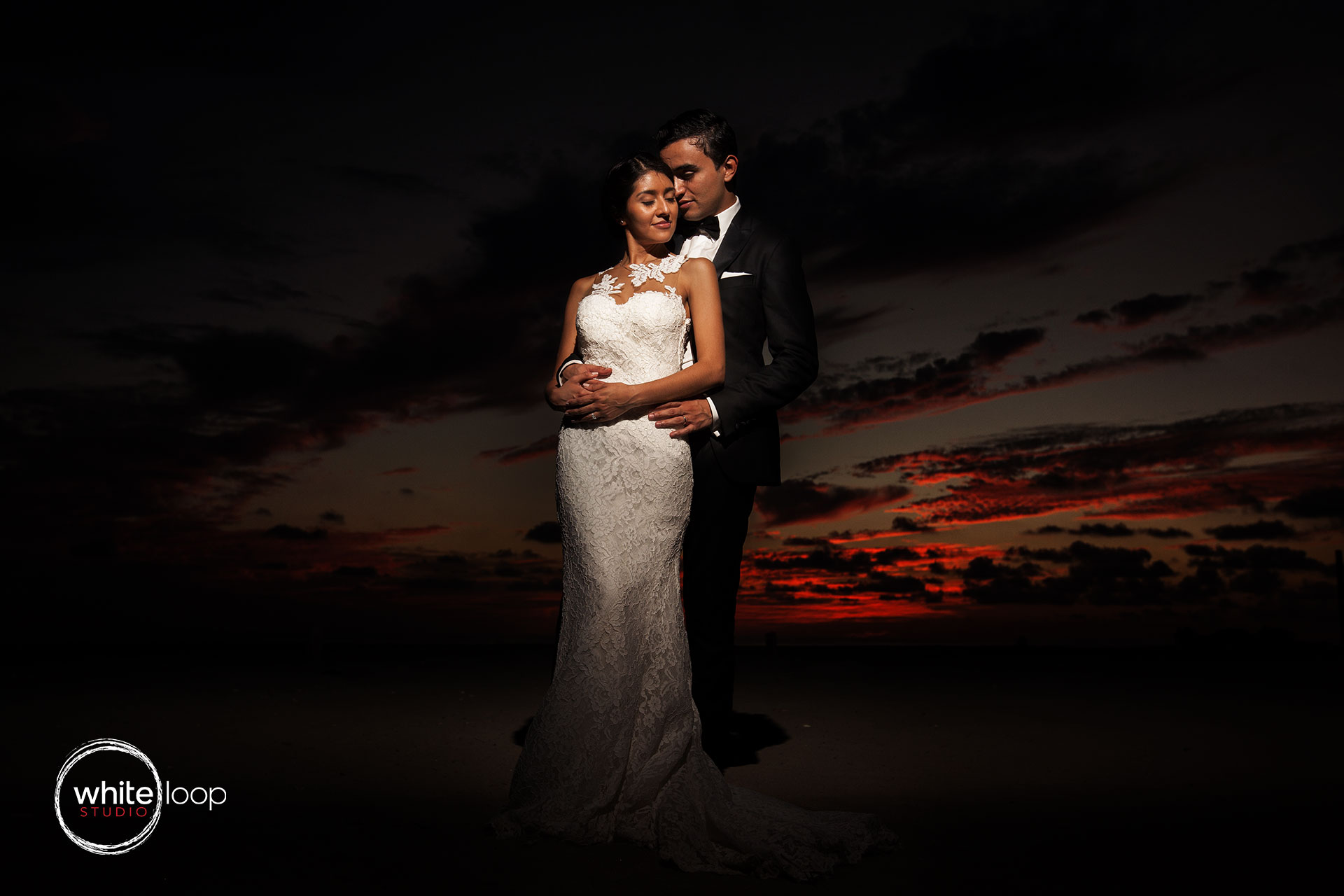 The bride and groom embracing in a landscape against a red sky of sunset.
