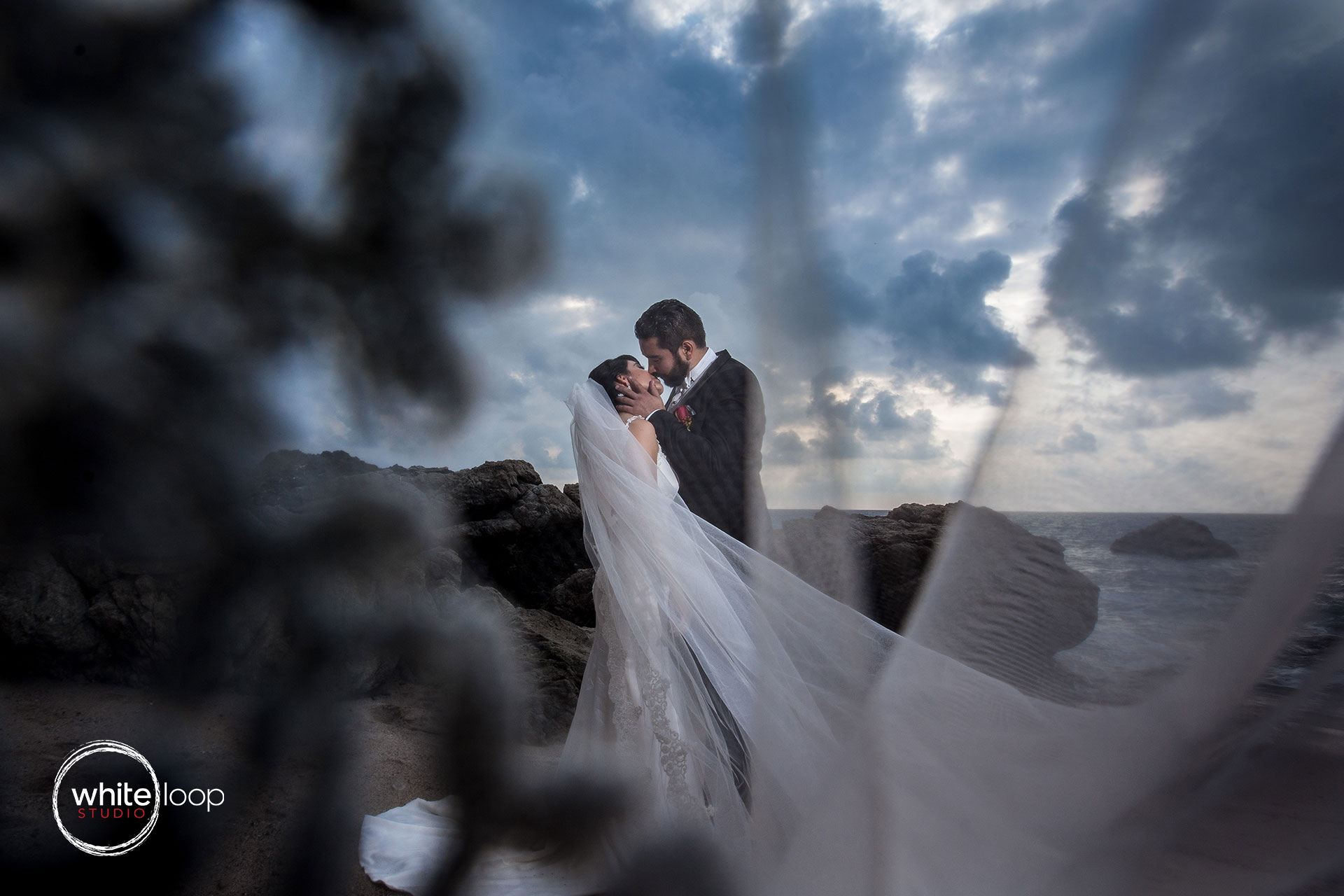 The bride and groom kissing on a rocky mexican landscape overlooking the sea on a cloudy day.