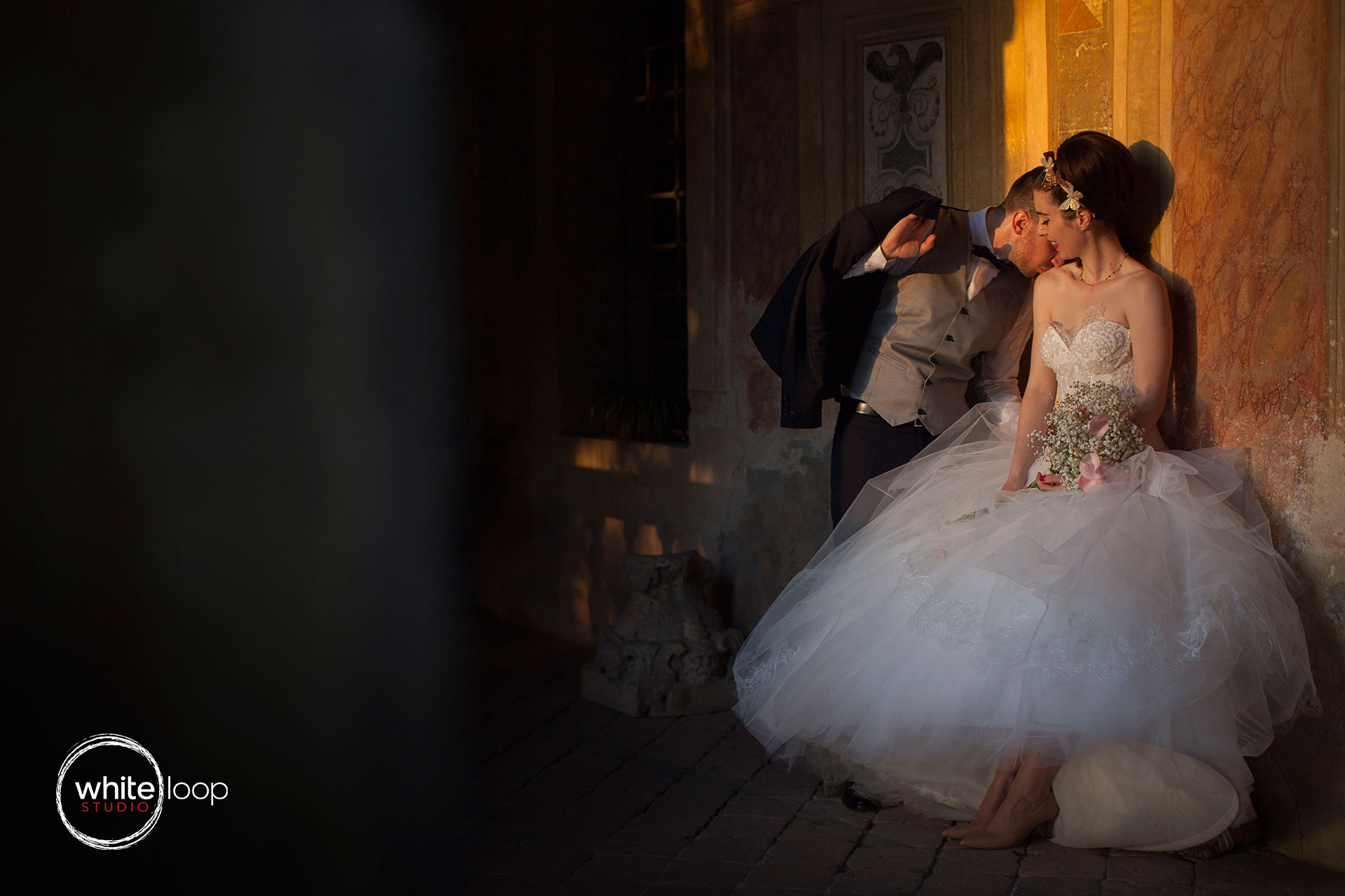 The grooms kissing the bride's shoulder while holding her bouquet of flowers while the light sunset illuminates the couple.
