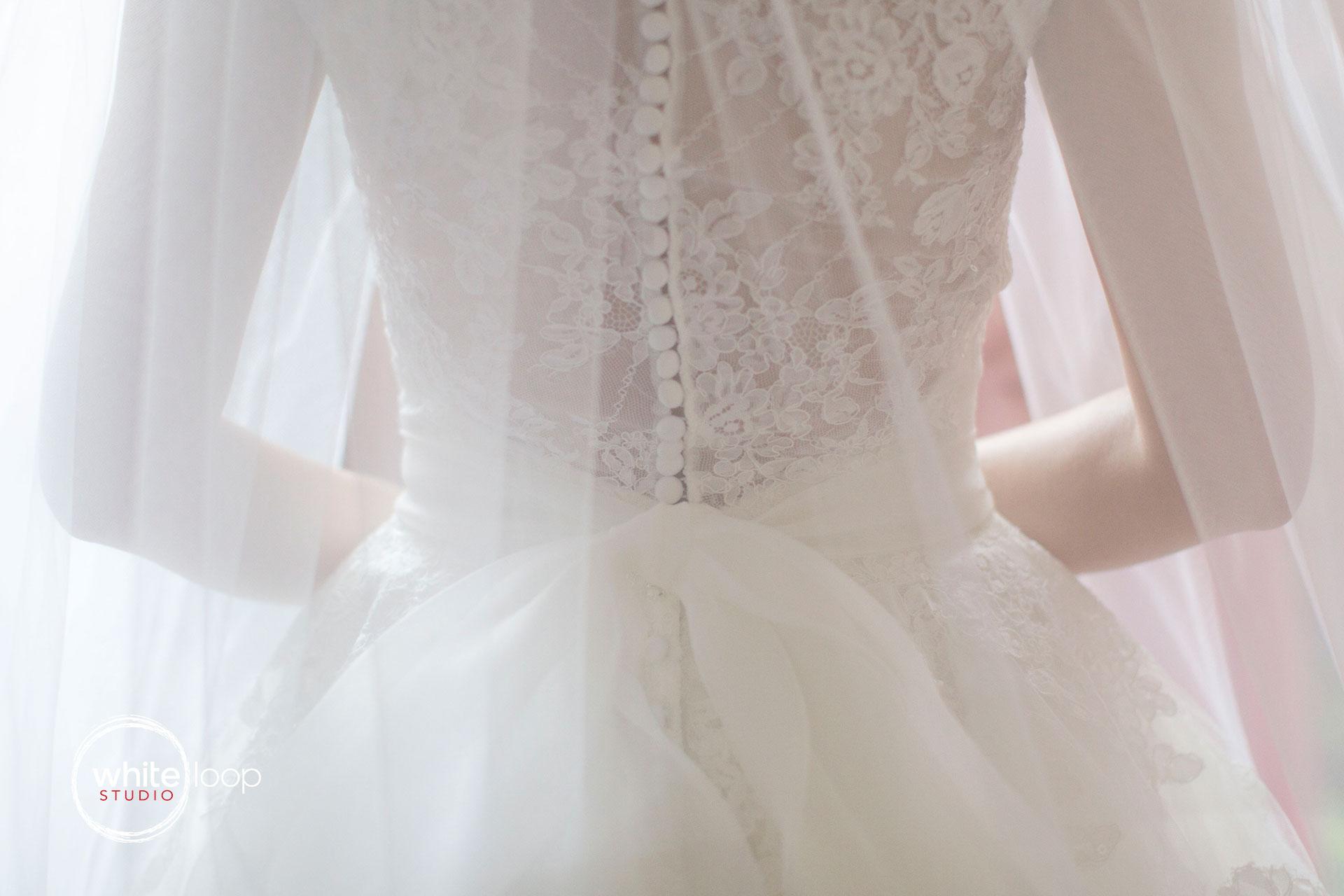 Behind the wedding dress under white veil