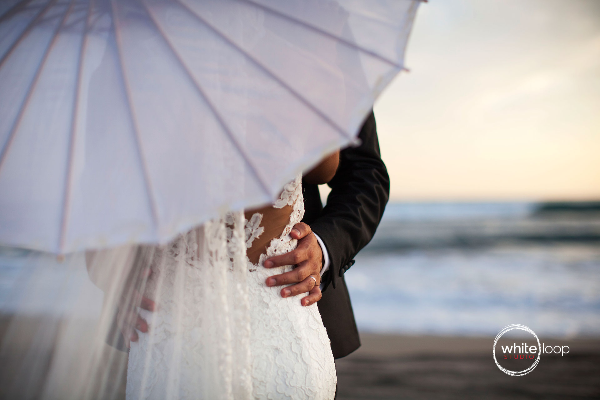 The groom holding the waist bride who carries an umbrella along the beach.