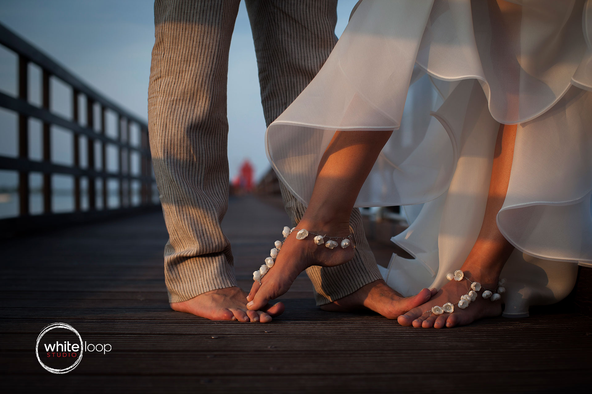 The feet of the couple barefoot with some accessories in the dock.