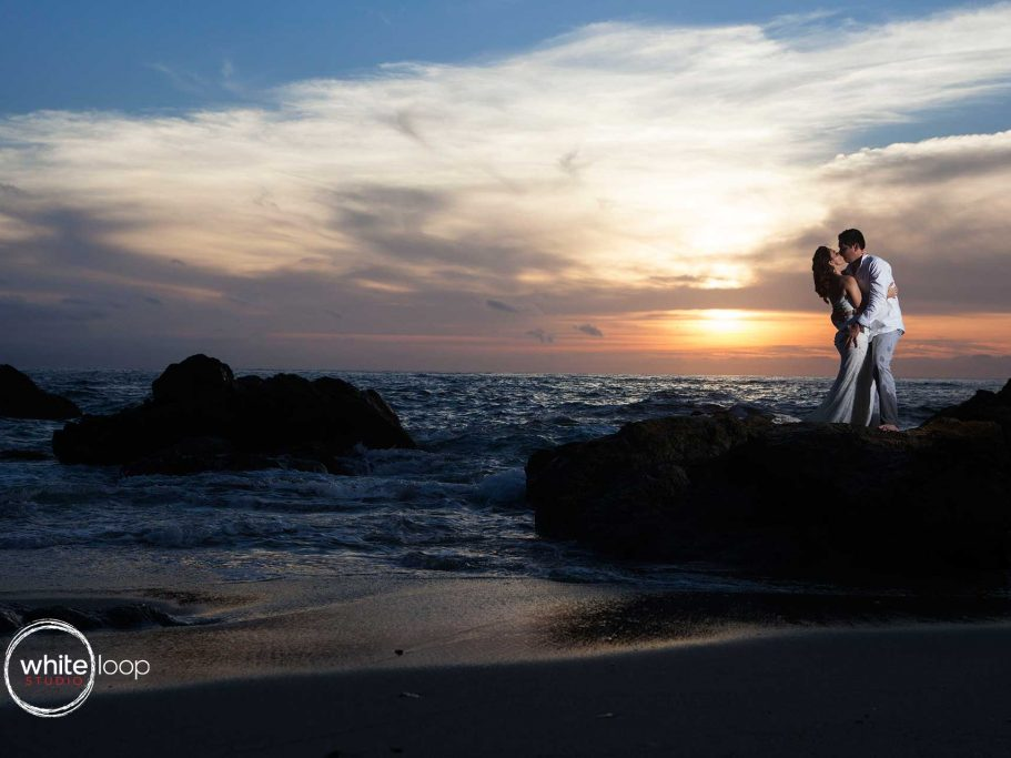 The groom and the bride embrace on top of a rock on the seashore.
