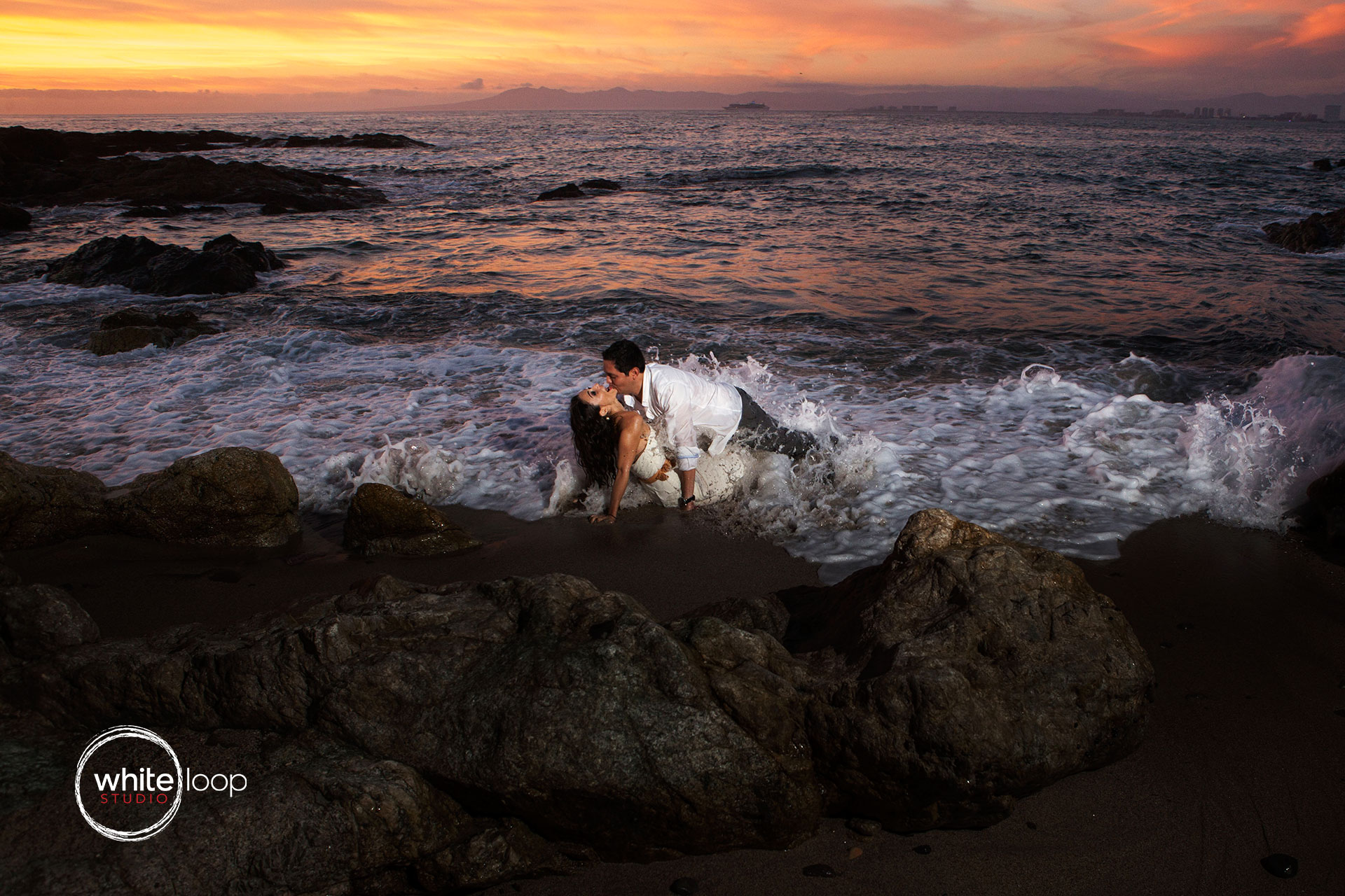 The bride and the groom getting wet at the seashore of the ocean.