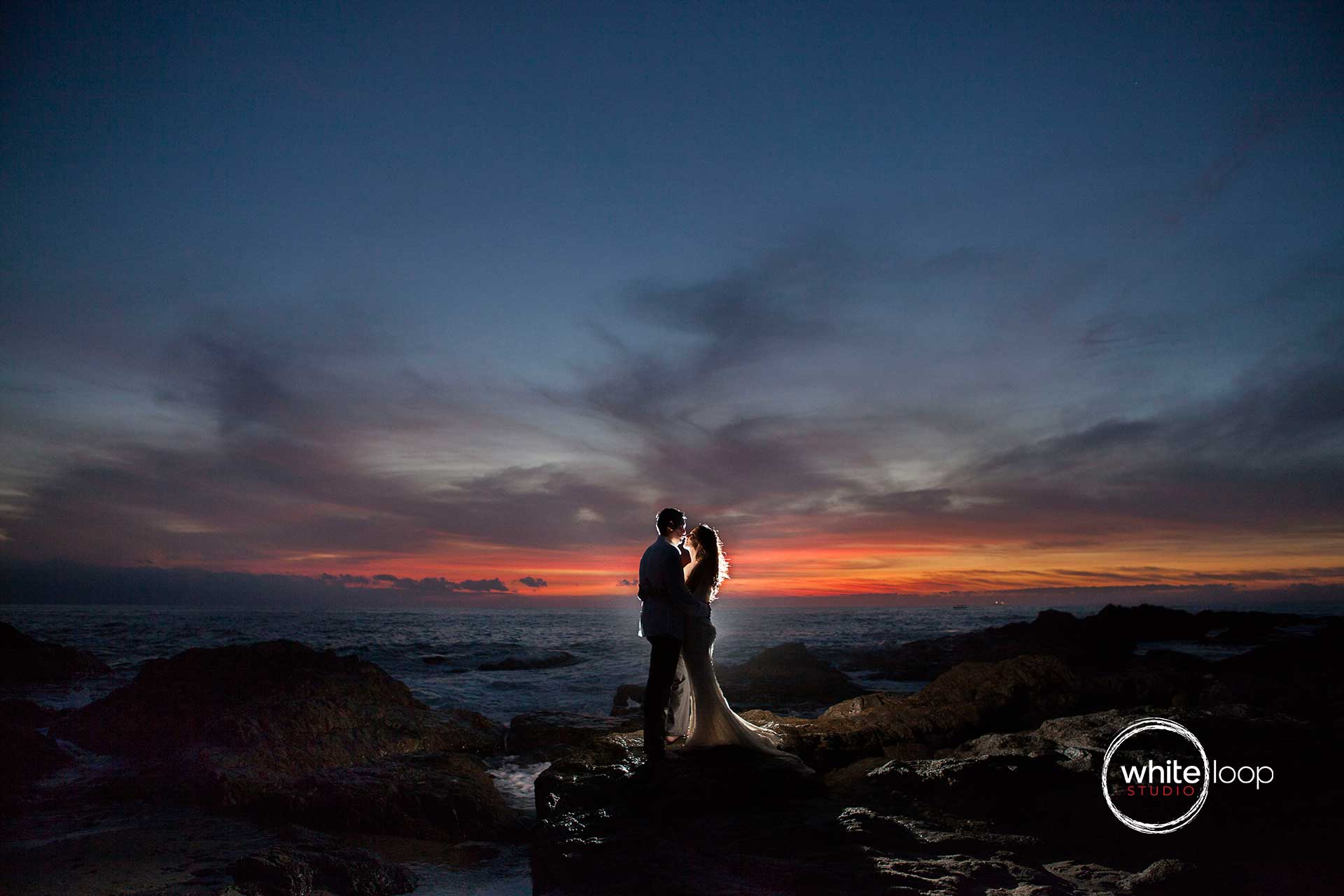 The bride and groom in the middle of the rocky seashore, in a sunset, illuminated with a lamp.