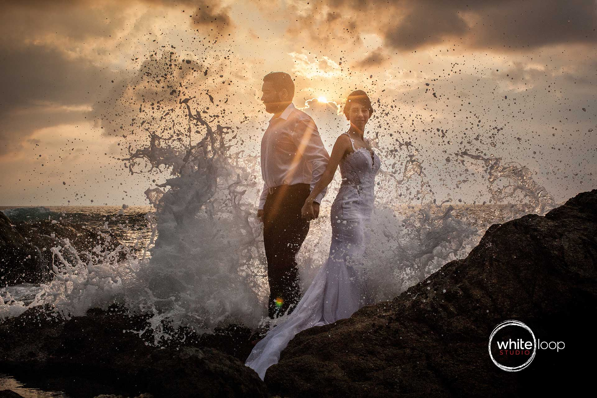 The bride and groom holding hands at the tip of a rock while an ocean wave knocks and splashes.