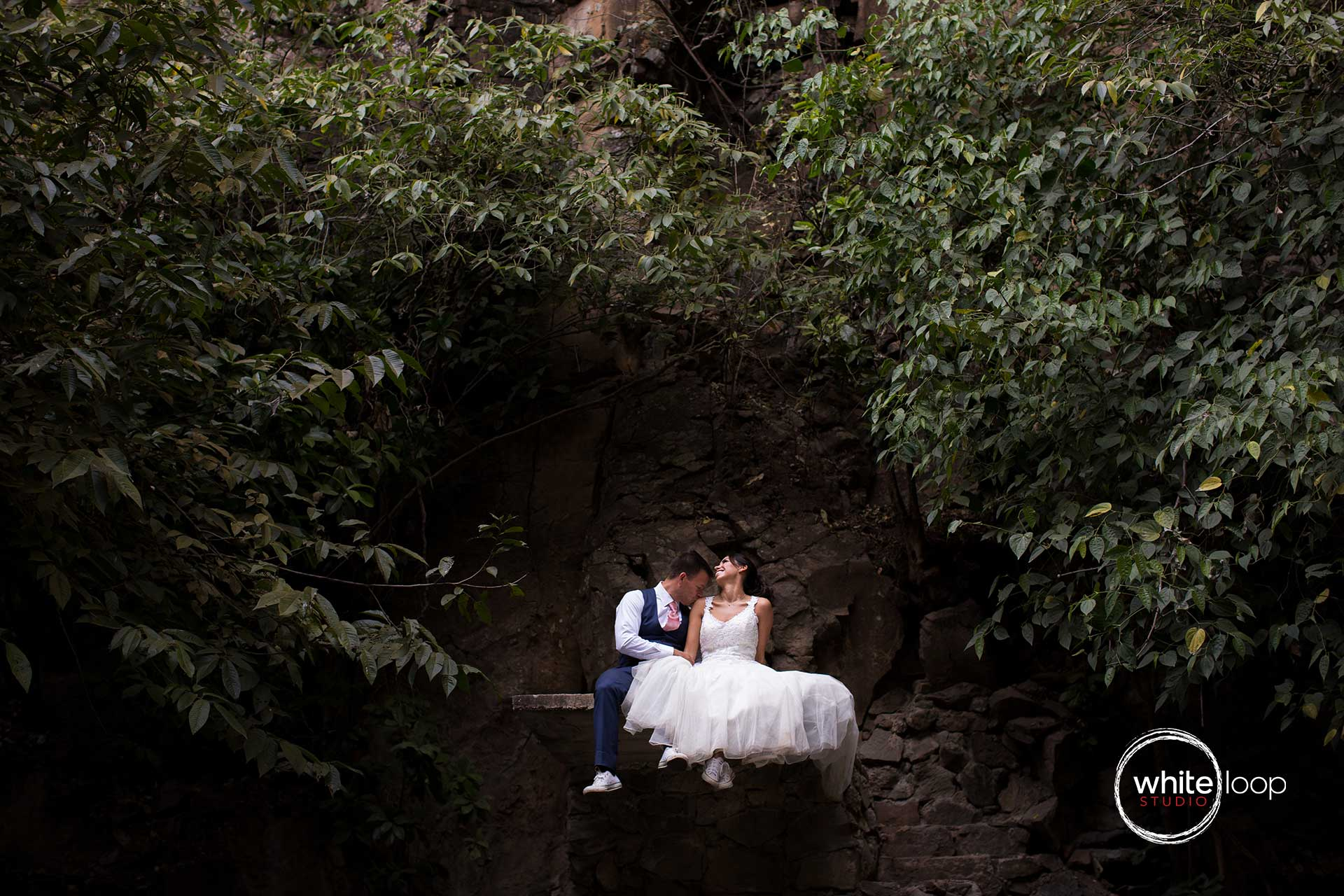 The bride and groom enjoying their love sitting on top of a mountain.