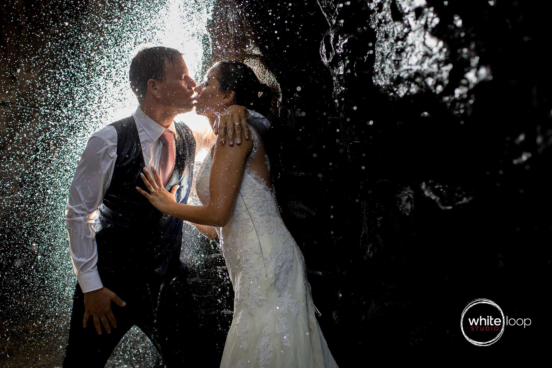 The bride and groom kissing under the waterfall. Illuminated by a light simulated.
