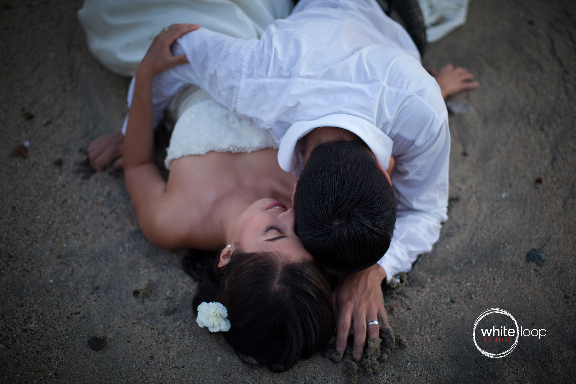 The bride and groom lying on the sand of the beach enjoying the their moment.