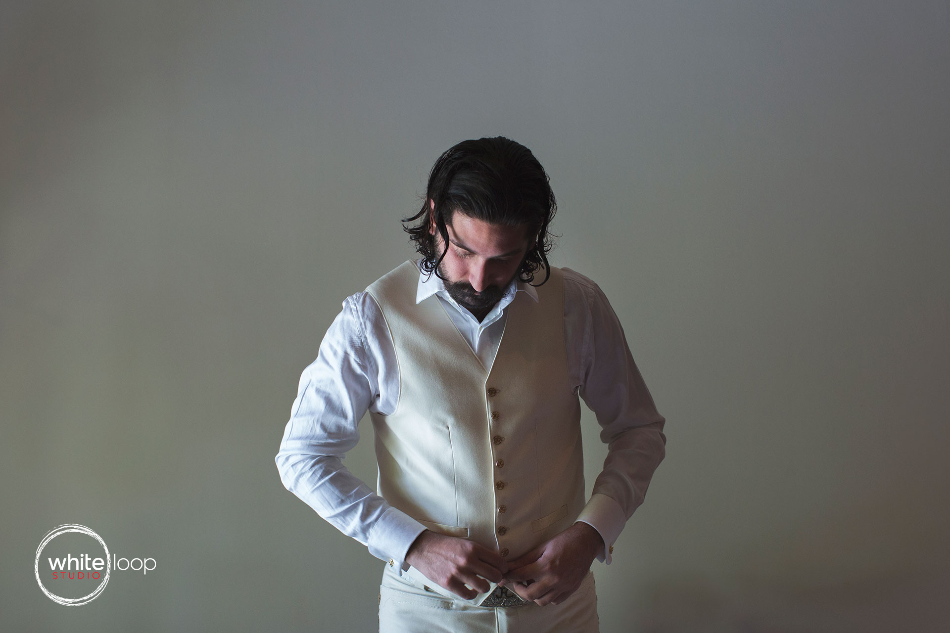 The groom is preparing for the big moment, adjusting his vest of the smoking, in a totally clear environment with a background of a white wall.