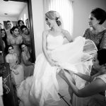 The close friends of the bride are adjusting and checking the final details of the dress.