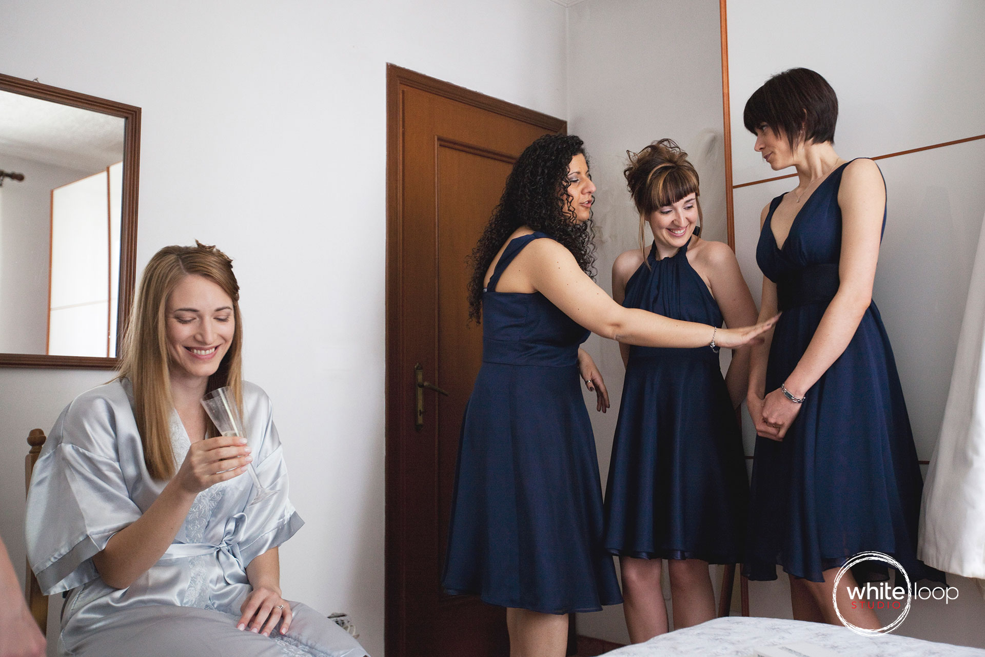 The bride enjoys the moment with her bridesmaids, with a glass of white wine, preparing for the wedding.
