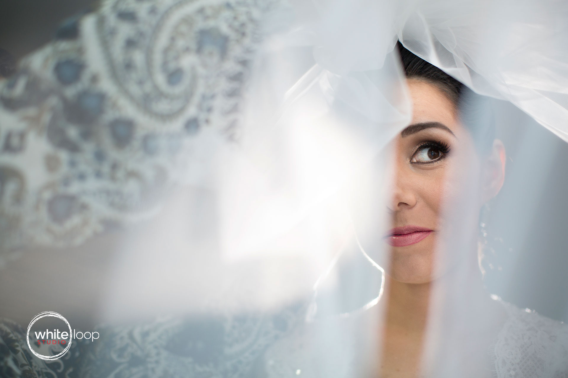 Photographing the beautiful bride under his own veil, taking a different perspective.