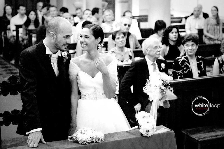 The bride talking with groom in the middle of the ceremony in the church, while mum is tenderly watching, projecting the picture in black and white as a symbol of elegance and finesse of the moment.