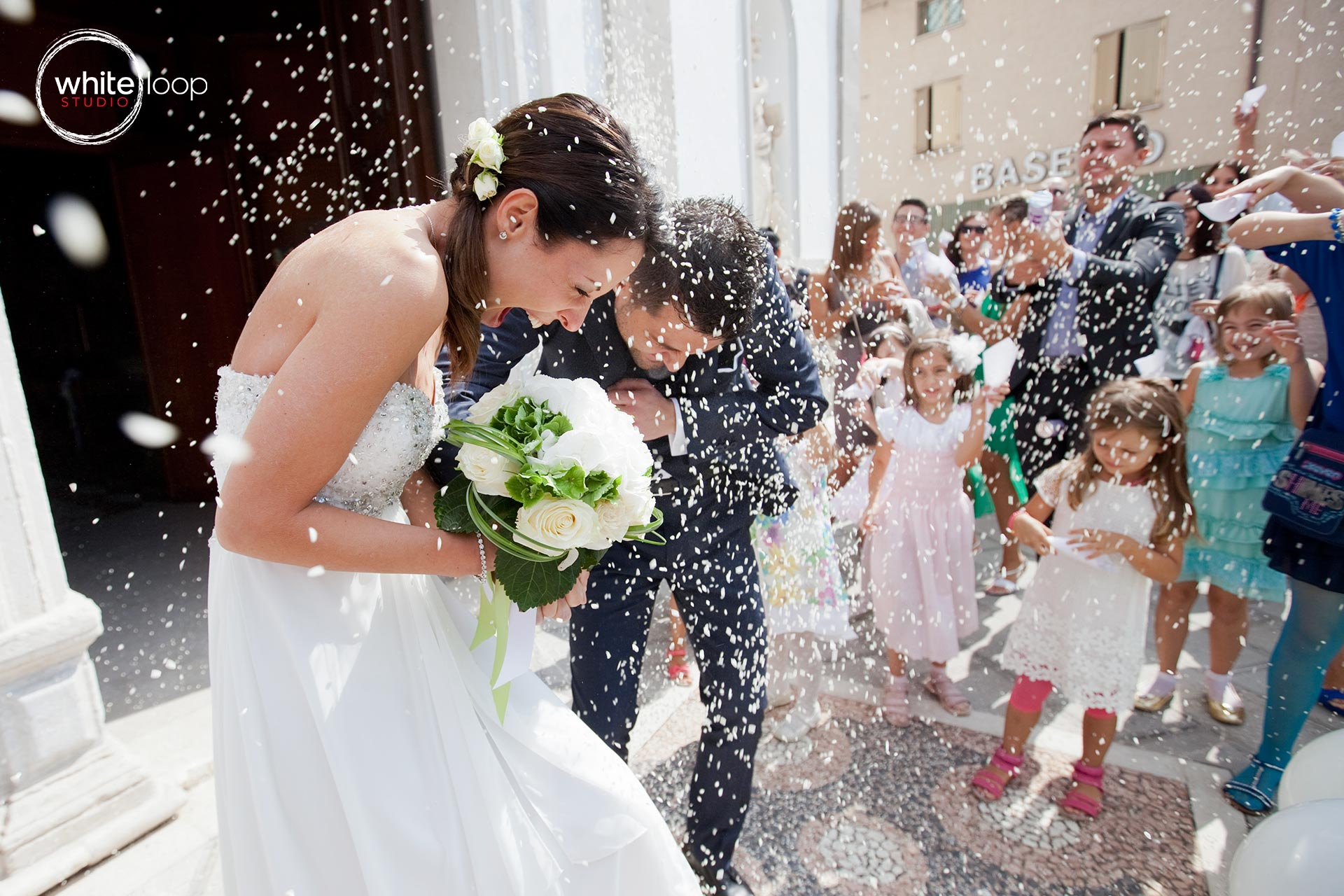 The bride and groom are celebrated outside the church, throwing rice as the wedding tradition.