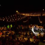 The guests appreciating the time of the first dance between the bride and groom, illuminated by the lights of the room.