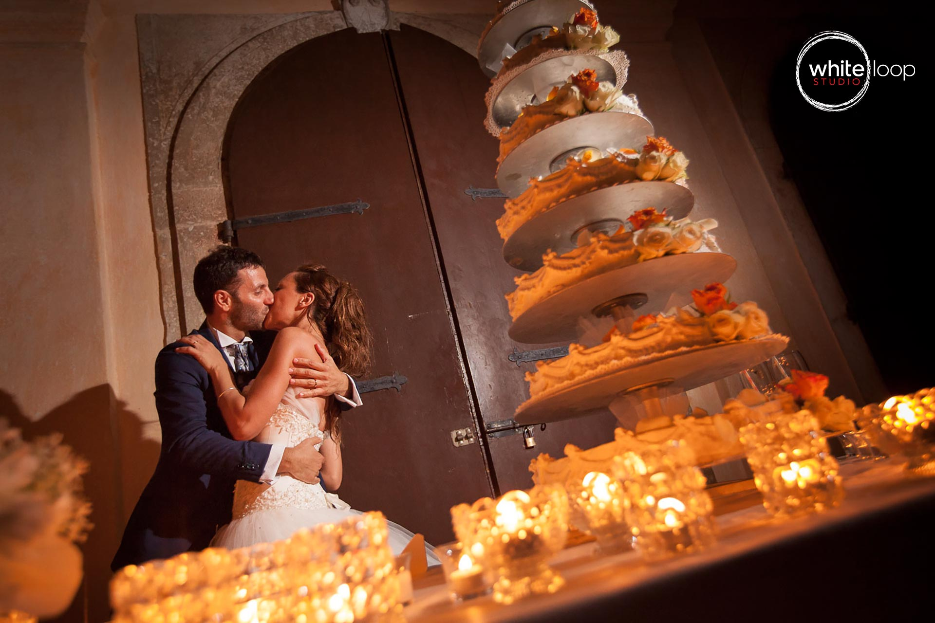 The bride and groom kiss on one side of cake with some lighting, defining a romantic and special moment.