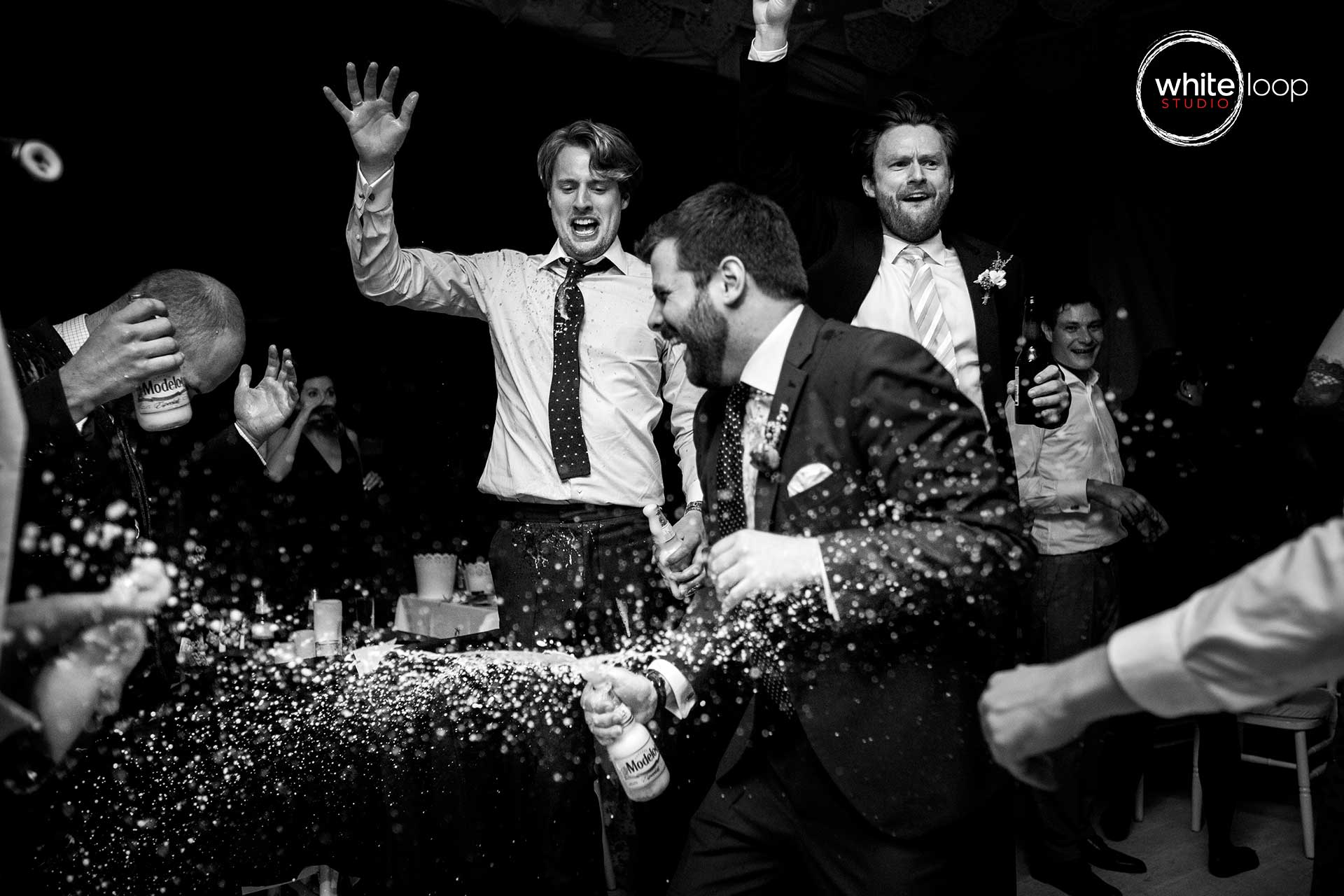 The groom celebrating and having fun in black and white with his german friends, uncovering a beer.