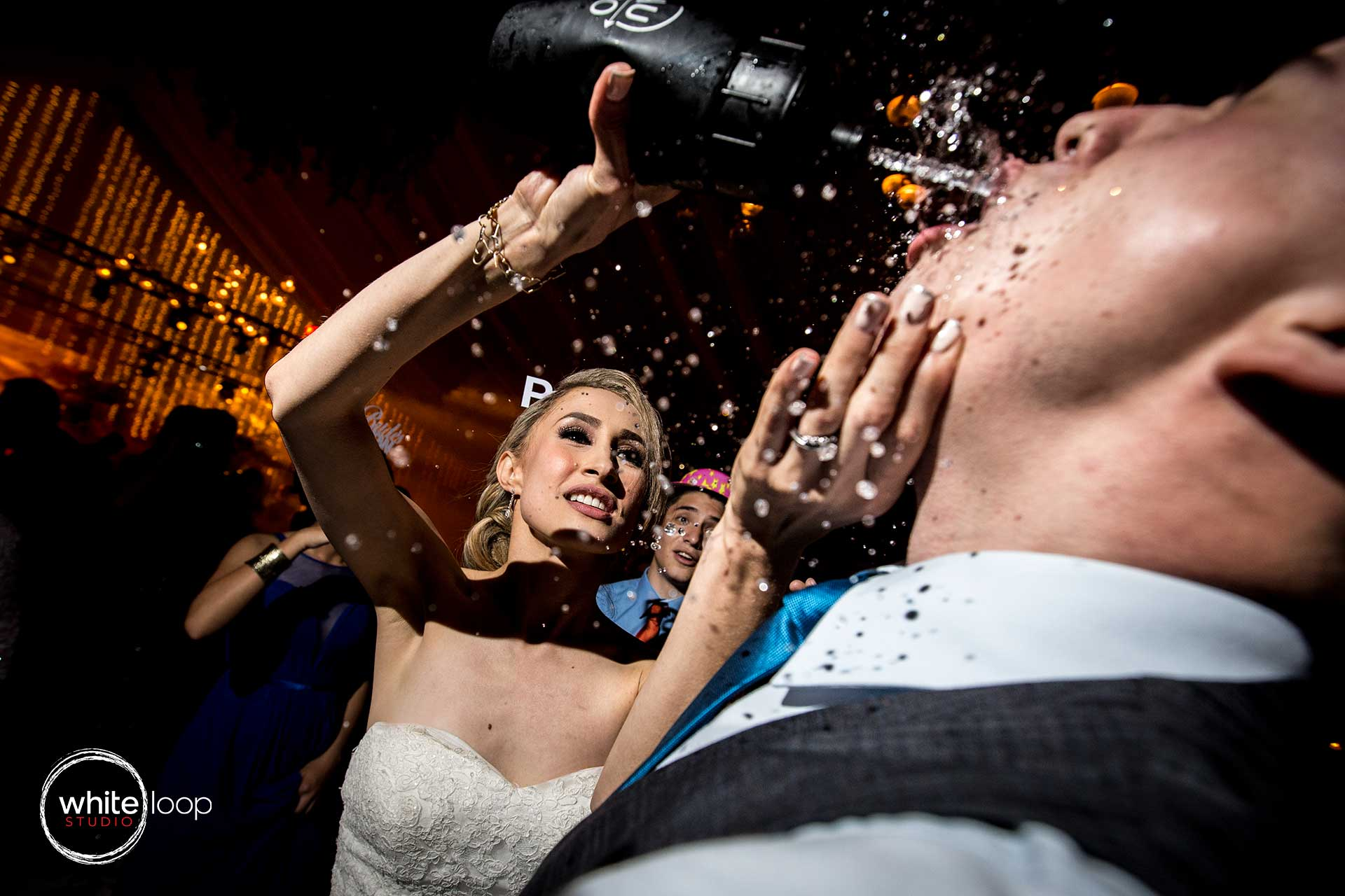 The bride giving a big shot from a thermos to the groom as they celebrate and have fun.