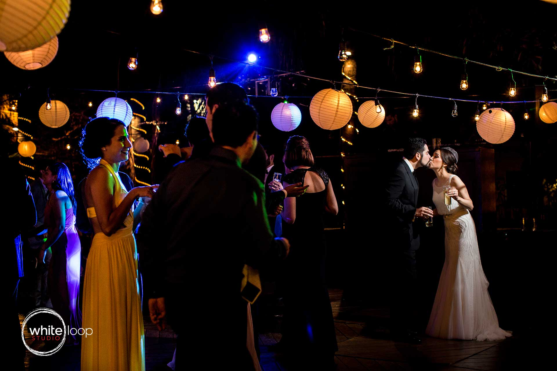 During the party and celebration with guests grooms are giving a kiss while light illuminates to capture the attention of the guests.