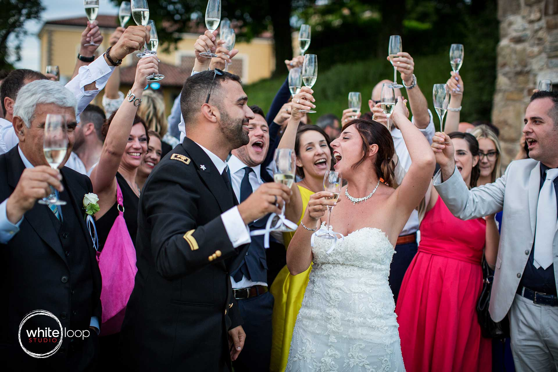 Everybody, the bride, groom and the guests are doing a big toast for the wedding.