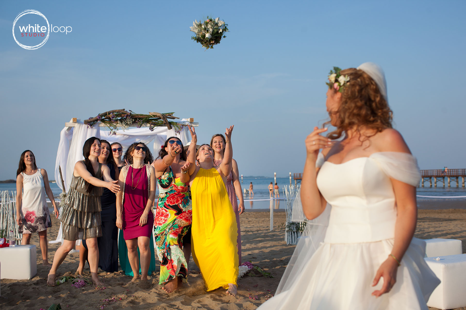 The bride is throwing the bouquet for some guests, as a tradition of who will be the next woman to get married.