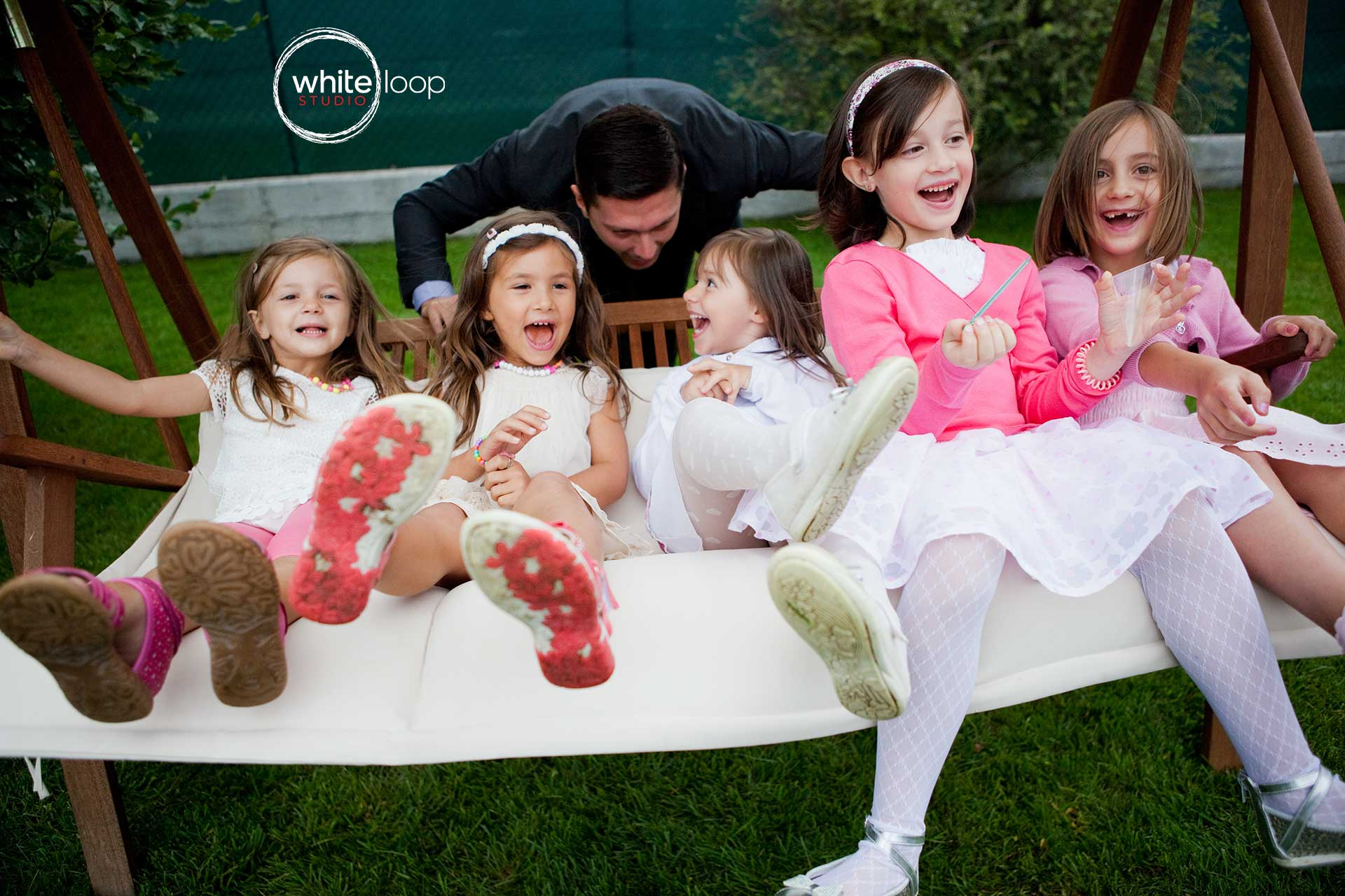 Here are some little girls having fun sitting in a big rocking chair and the groom is in the back playing with them.