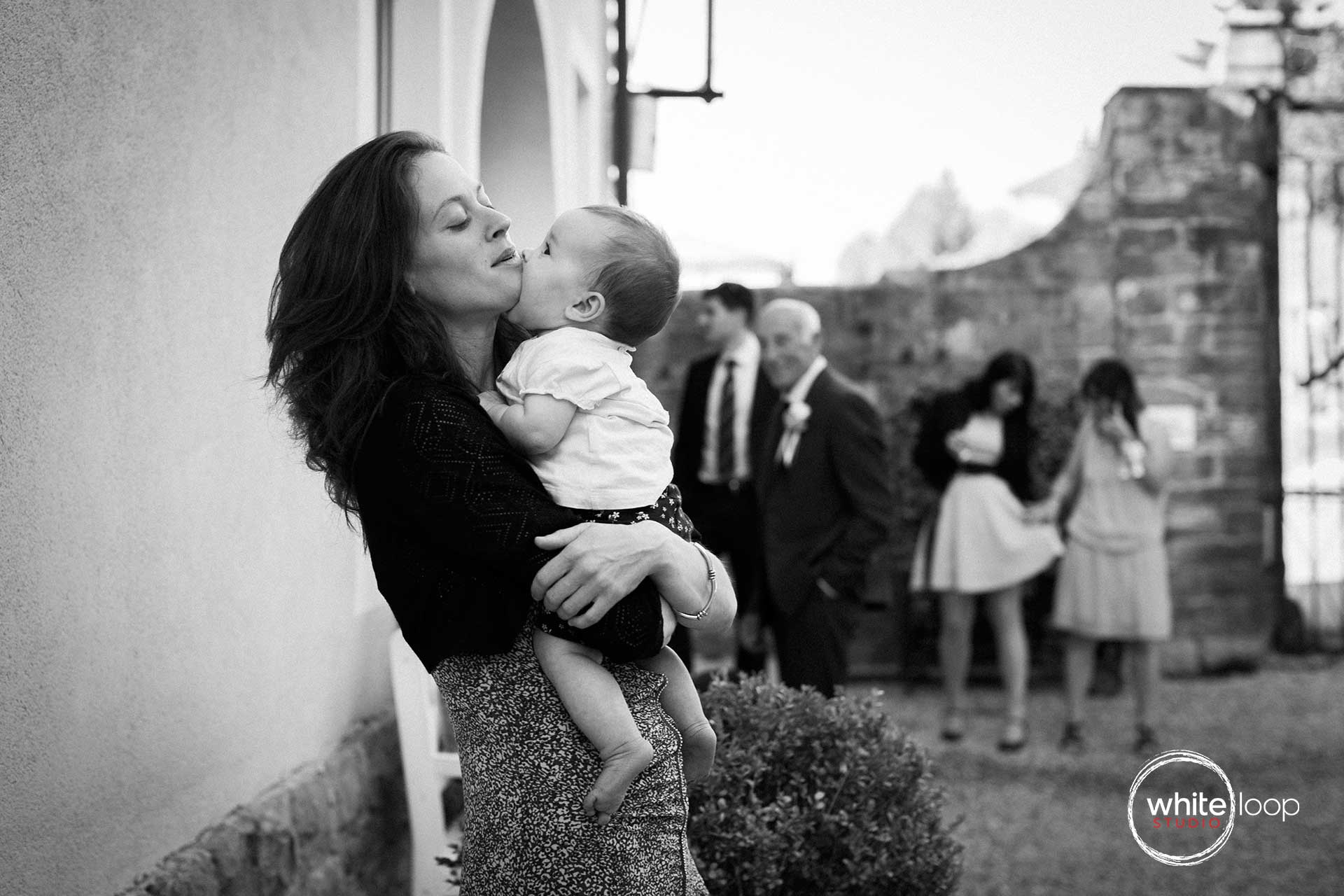 The very little baby is in the arms of his mother, giving a big little baby kiss in black and white.