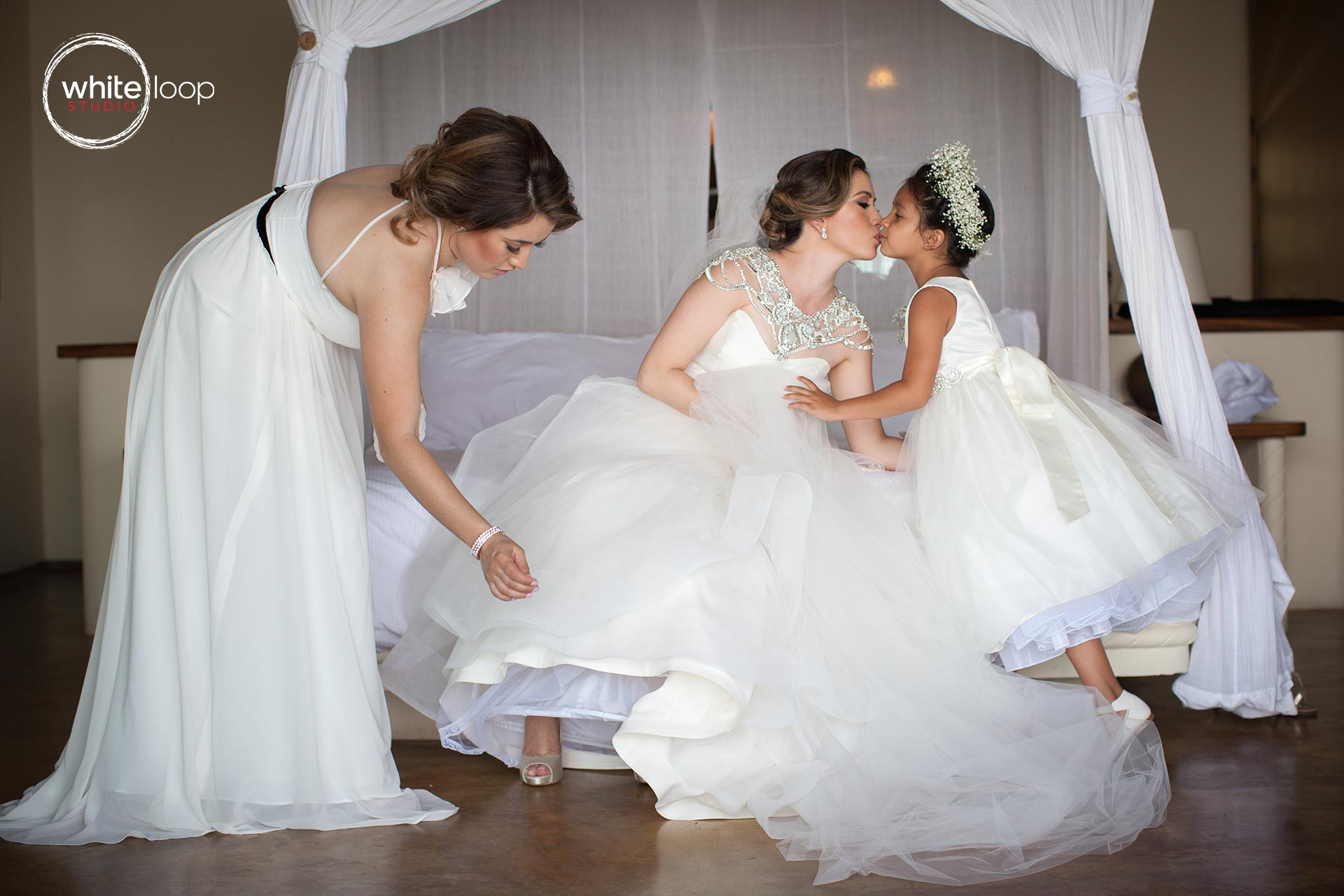 The bride is kissing her little bridesmaid with a maternal tenderness just before going to the church.