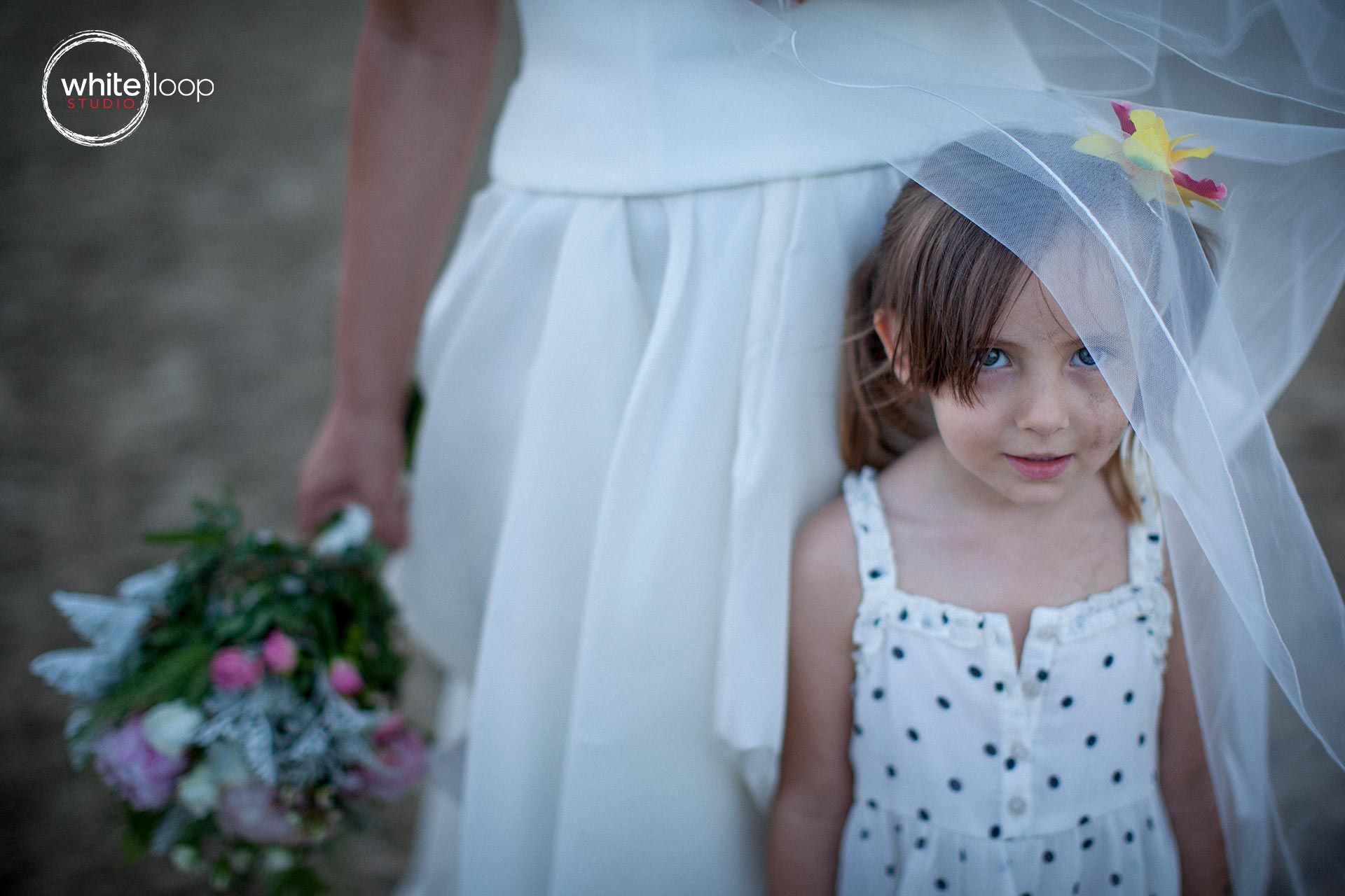 Here is a beautiful glance of a little girl under the vail of the bride just after playing on the beach.