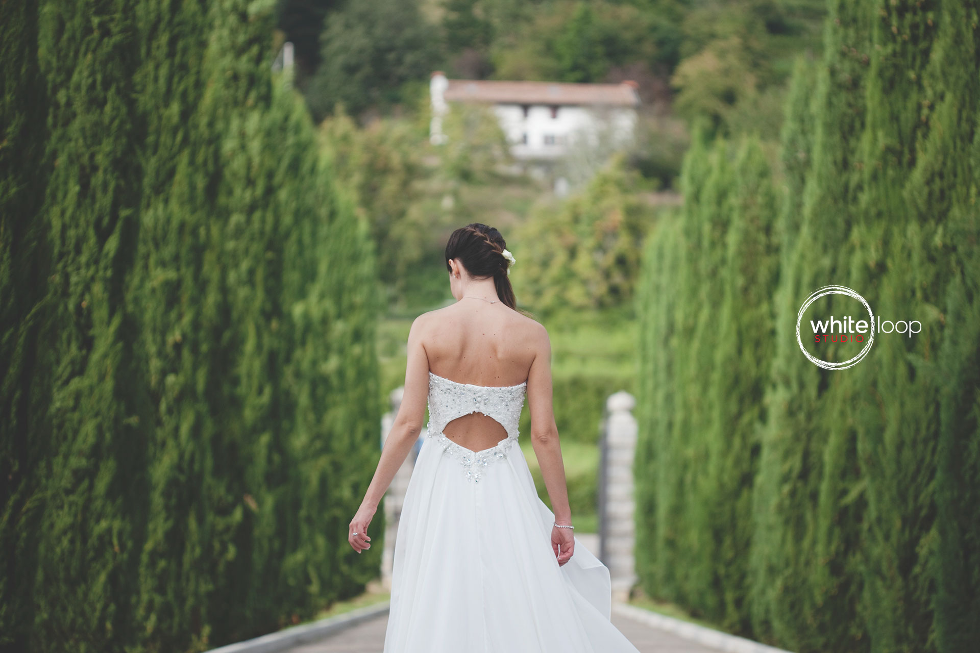 The bride is walking alone in this wedding dress, by a aisle full of little pine trees.