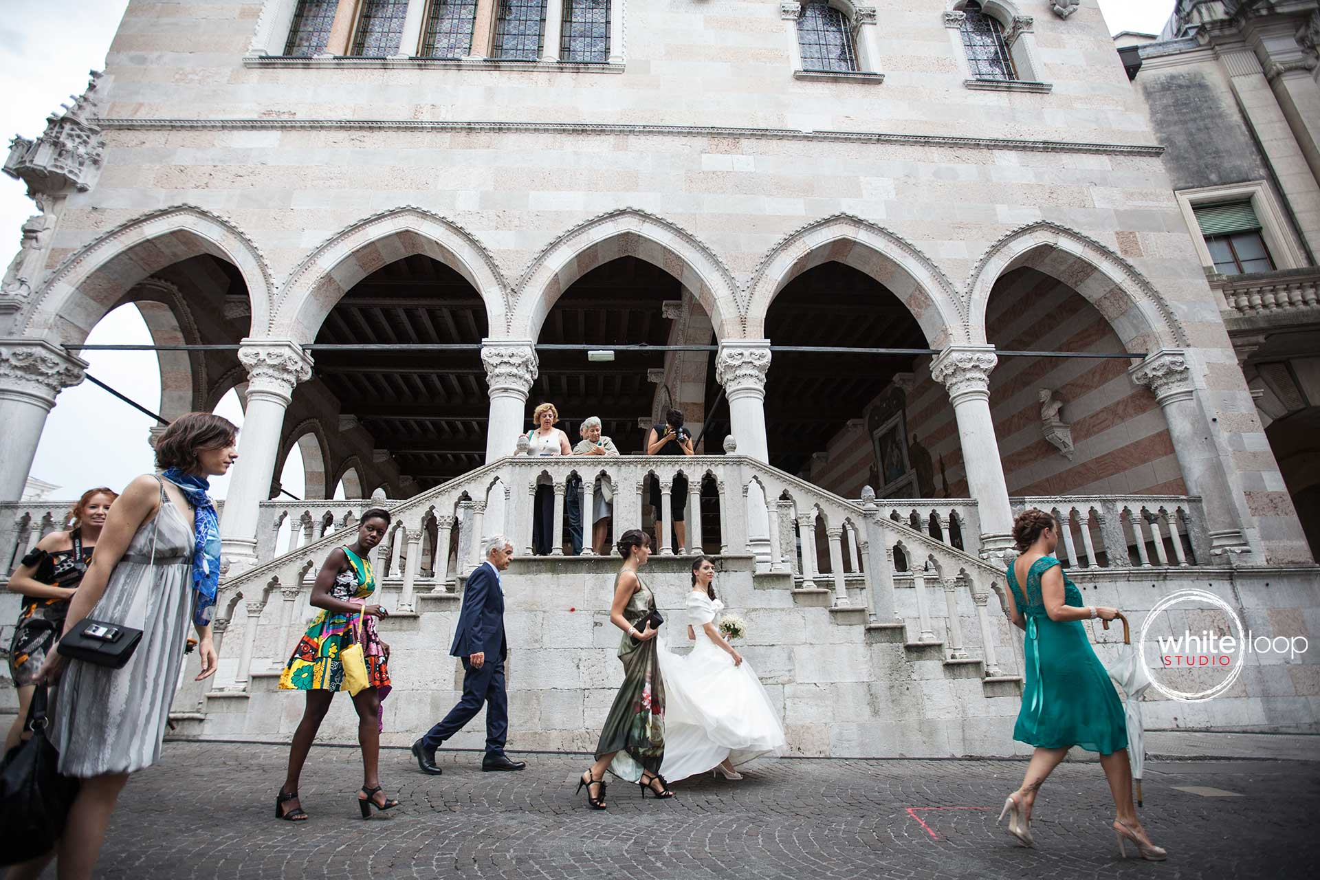 Some guests are walking to ceremony, carrying the bride along the streets of the historical centre of Udine, a small beautiful town in the North of Italy