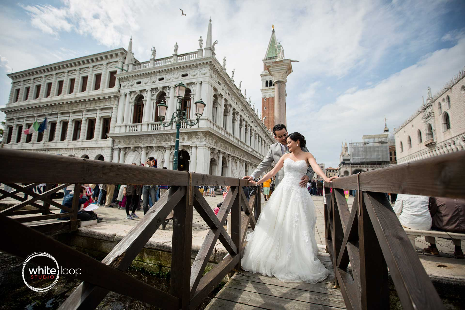The bride and groom are holding each other over a famous dock in Venice, just in front of one of the most popular and romantic square in Italy: Piazza San Marco