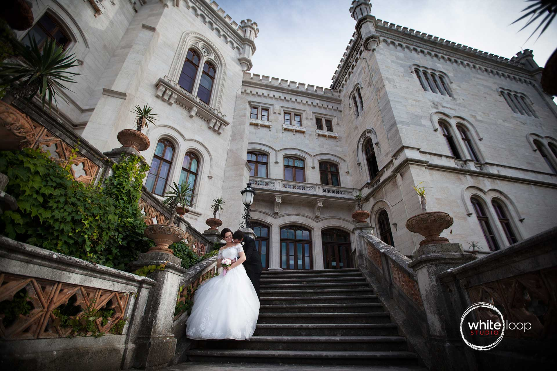 The bride and groom are holding each other with love outside of the Miramare Castle in Italy