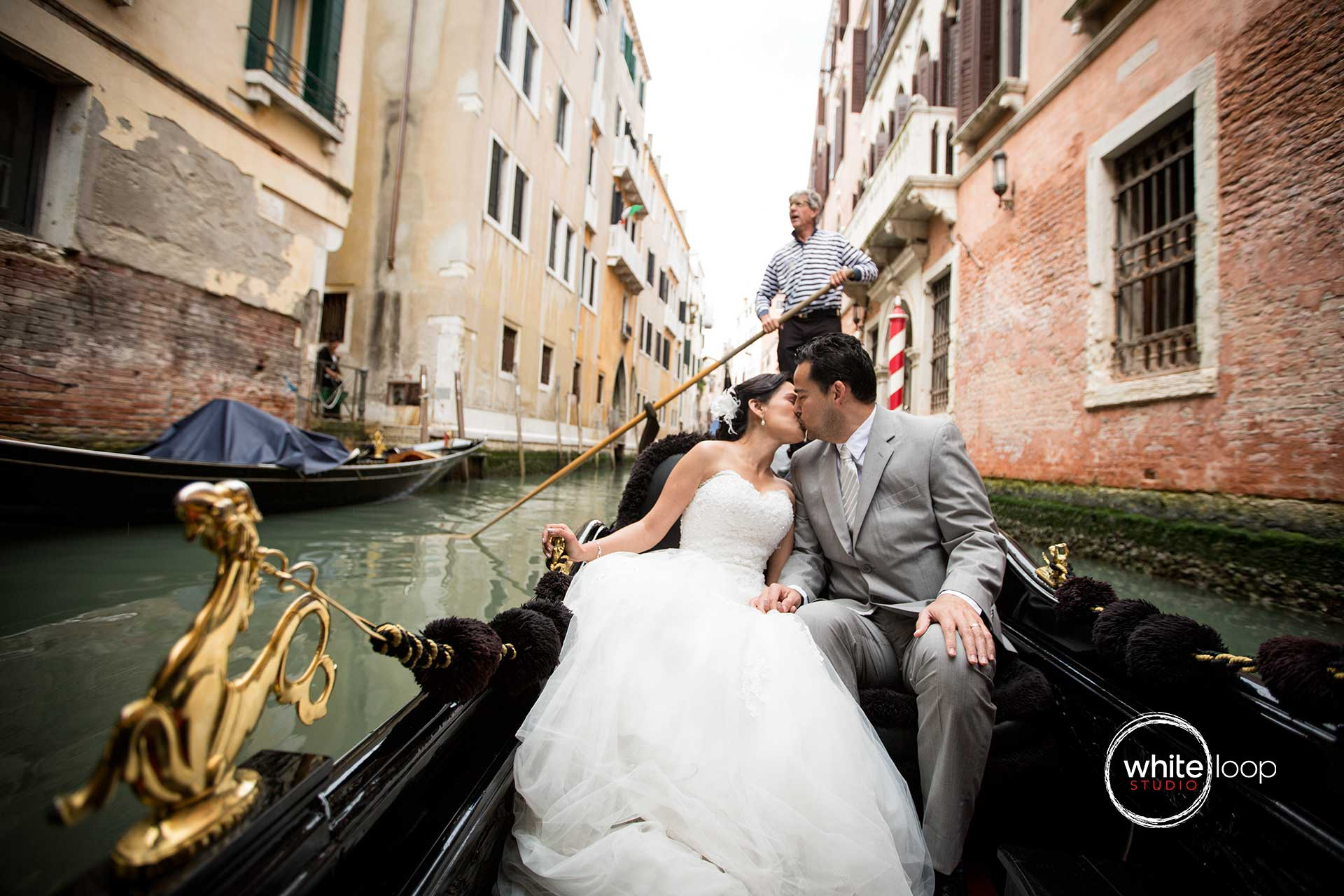 The bride and groom are kissing in a traditional Venetian gondola, meanwhile they are crossing the beautiful city of Venice in Italy.