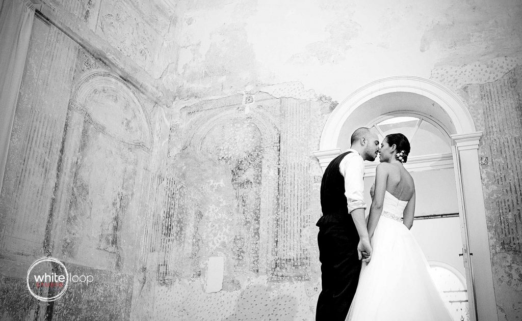 The bride and groom are kissing in black and white in an ancient room with frescos in the historical Italian environment.
