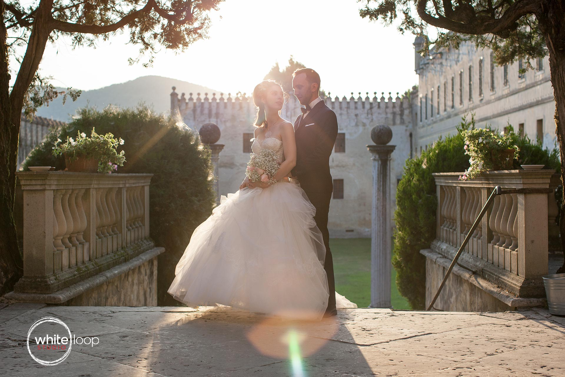 The bride and groom are holding each other in the stairs of the beautiful ancient castle, with a natural backlight.